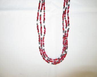 Red triple-stranded beaded necklace with silver and crystal accents