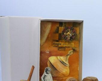 Art box:diorama réalisé dans une boite d'allumette.Assemblage, jeu d'enfant, roulette et toupie.