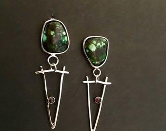 """Turquoise dangling silver """"V""""holding a garnet earrings"""
