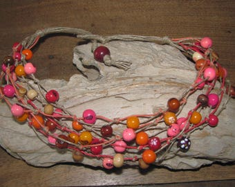 Short necklace with Acai seeds in red, orange and pink knotted in linen thread