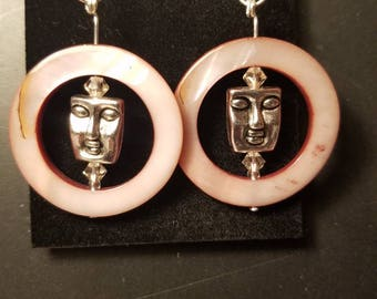 Meditative faces in circles made of pink tinted shell