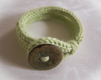 Knitted green bracelet with a large button
