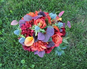 Fall boho bouquet in burgundy and rusty orange roses dahlias real touch calla lilies.  Burgundy eucalyptus olive branches and blue thistle