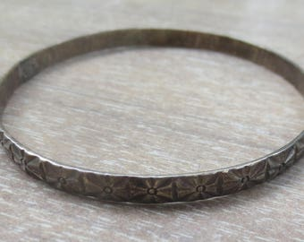Thin silver bangle bracelet with carved design measures 8 inches around