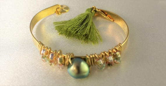 golden plated bangle with a green iridescent swarovski pearl, bicones swarovski and a tassel charm