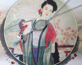"""Oval necklace, Japanese paper with floral pattern and """"Art Déco"""" charm."""