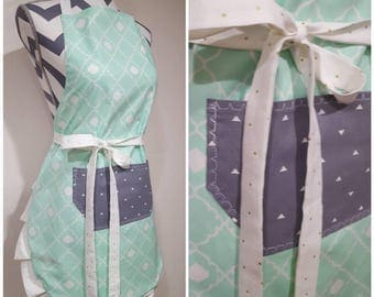 Adult apron. Woman's apron. Mint and white backing with gray pocket. Ties and frills have tiny gold polka dots on white.
