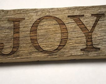 Vintage barn wood with the word joy engraved on it.