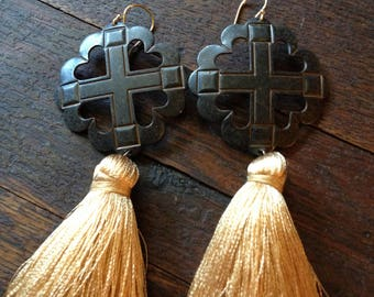 Golden silk tassels on blackened copper cross medallions.