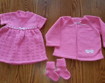 Lacy pink baby's dress, sweater and sock set