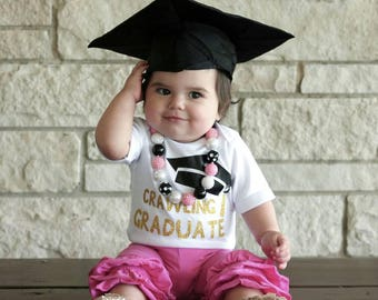 Crawling graduate bodysuit with black graduation cap and gold writing, comes in sizes 6 months to 2T. Crawling bodysuit