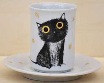 Cup and saucer breakfast cat with gold stars.