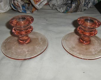 a pair of pink candle holders