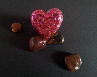 ring has pink heart glitter resin