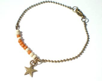 Star styled small beige and orange beads and charm bracelet