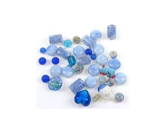 An assortment of blue shaped glass beads variable.