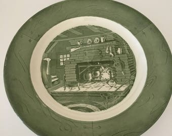 Mid-Century Royal Co. Colonial Homestead 10 inch dinner plate, green & white dinner plate with colonial fireplace scene, rifle on fireplace