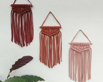Three small macrame wall hangings in pink, copper/chestnut and conker red