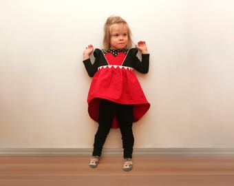 Red and black and white polka dot toddler top with ruffle sleeves and extended back. heart shaped pocket, bow on back. queen of hearts.