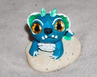 Little grumpy polymer clay mermaid dragon sitting on a beach stone
