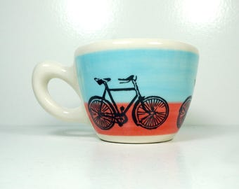a 12oz cup painted in a color block of blue & red-orange with Dusty Road Bike prints READY TO SHIP