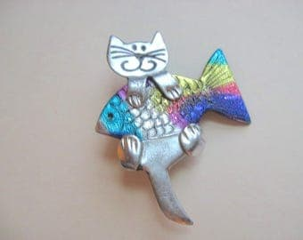 Cat holding a Rainbow Fish Pin Brooch