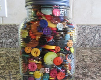 Large glass jar full of colorful buttons with screw on lid