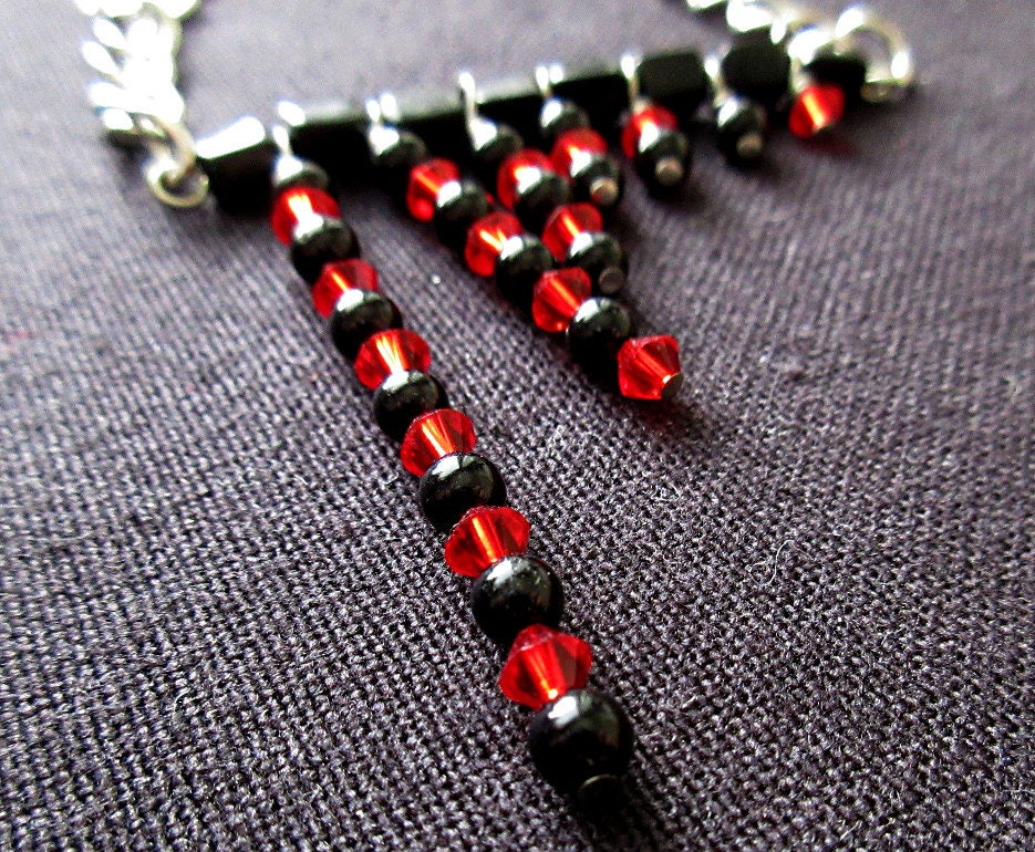 A beaded statement necklace featuring round and rectangular black glass beads and red Swarovski crystals counting out Fibonacci numbers. It's Harley Quinn mathart!