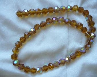 Bead, glass, Honey Brown AB, 8mm faceted round.  Sold per 13 inch strand.  There are 47 beads on this strand.