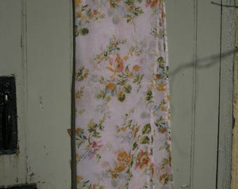 A Large 100% Cotton Scarf in a Pretty Soft Pink background, printed with Multi-Coloured Flowers.