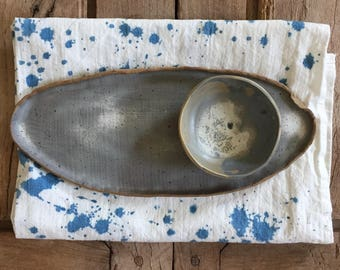Oblong blue gray speckled serving platter, with unattached condiment bowl.
