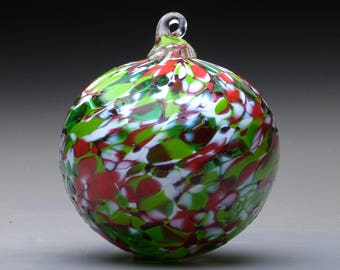 hand made blown glass Christmas ornament in tones of red, green, and white, Holiday
