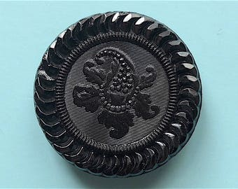 Black glass Paisley button, antique.  A Paisley centre with a linear background & a decorative border, 4 hole metal shank. c1900.
