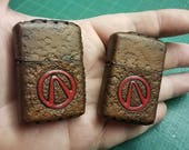 """Two """"Borderlands"""" leather lighters."""