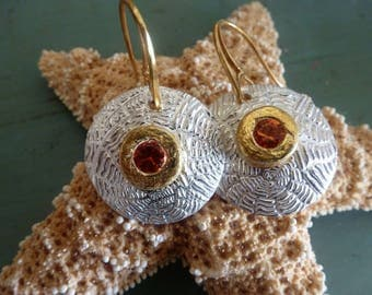 Silver Shield Earrings are beautifully textured convex circles centered by 22 kart gold bezeled topaz gems on Vermeil French earwires.