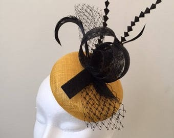 Beautiful yellow button base fascinator with black sinamay loops and flowers!