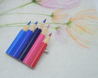 Large brooch with pink and blue colored pencils