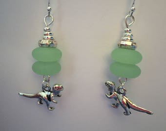 Green sea glass and silver beaded earrings with dinosaur charm.