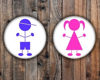 Gender reveal pins.  Pink and blue stick figures.
