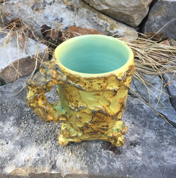 ceramic mug in golden yellow, navy blue, and melon green