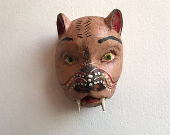 Pink animal with fangs, decorative mask.