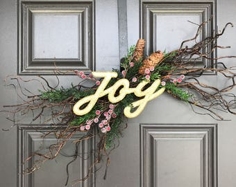 "Rustic Christmas decor; branch with evergreen, berries and gold ""joy"" lettering"