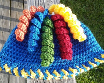"""New crochet baby hat for 6 to 18 months in royal blue with """"candy cane"""" edging and 5 colorful curly ques that move on top"""