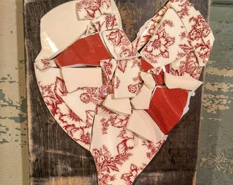This broken and beautiful heart is mounted on an old sanded wooden board. It has pieces of broken pottery in res, ivory and red floral.