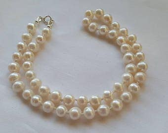 Natural freshwater cultured pearl necklace hand knotted with silk and finished with sterling silver