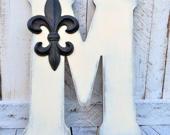 large wooden letters; letter M; distressed, whitewashed with cast iron fleur de lis