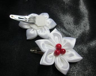 Adorned with a white satin flower with a hair clip is adorned with three red bead