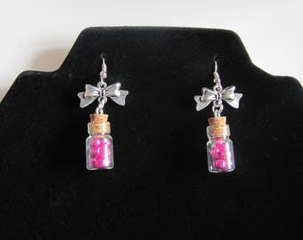 Glass vial earrings and pink pearls as well as his bow in metal silver