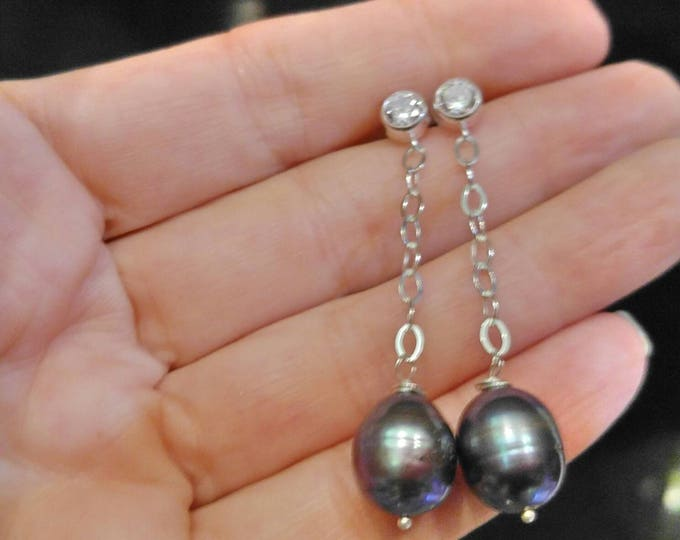 Black Tahitian pearl earrings in silver. Silver post earrings that dangle and drop. Gray pearls dangle from a silver chain. Silver post