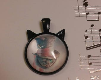 Kitty Kat shaped pendant featuring winking cheshire cat wearing a mad hatter hat. Bubble glass.